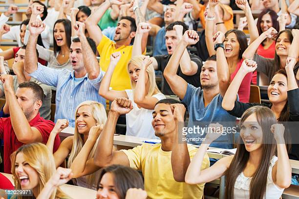 successful students sitting with raised arms. - graduation crowd stock pictures, royalty-free photos & images