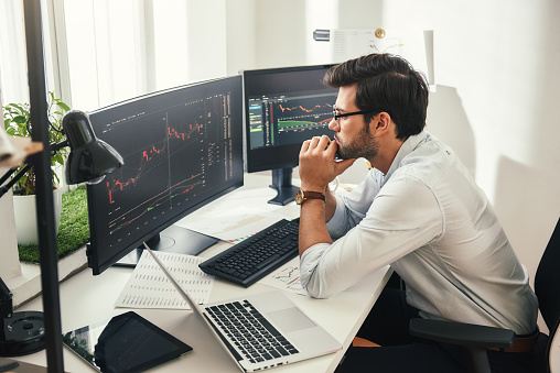 Successful trader. Back view of bearded stock market broker in eyeglasses analyzing data and graphs on multiple computer screens while sitting in modern office. 1147352183