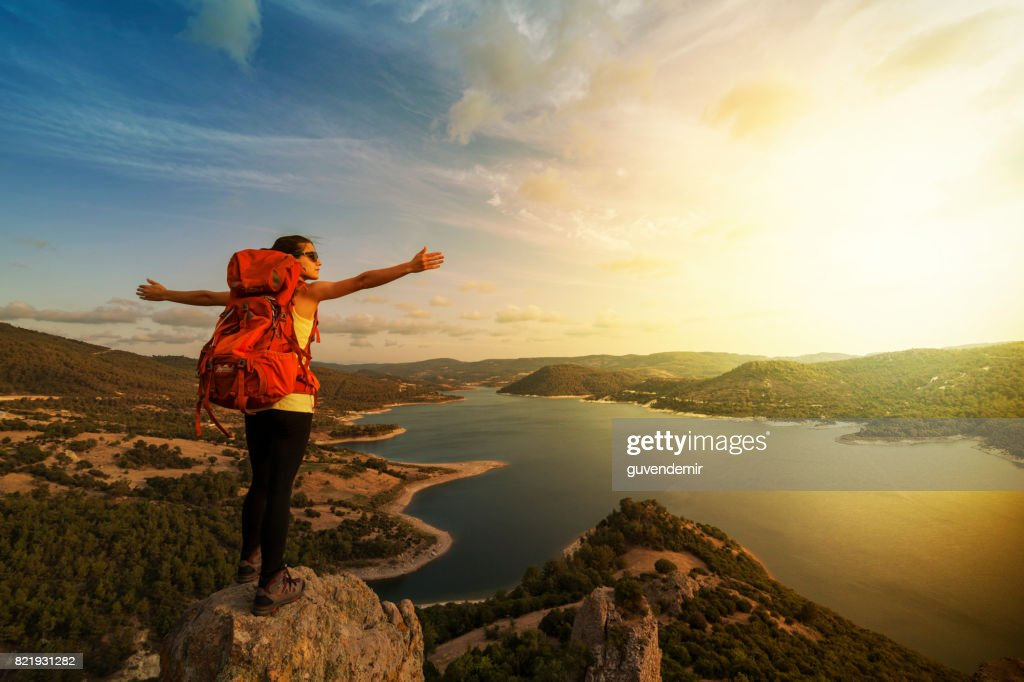 Successful woman backpacker enjoy the view at mountain peak : Stock Photo