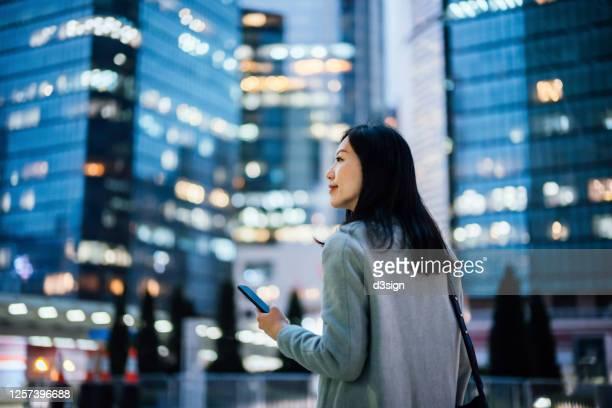 successful young asian businesswoman using smartphone on the go in financial district after work, against urban city scene with illuminated corporate skyscrapers - constitution stock pictures, royalty-free photos & images