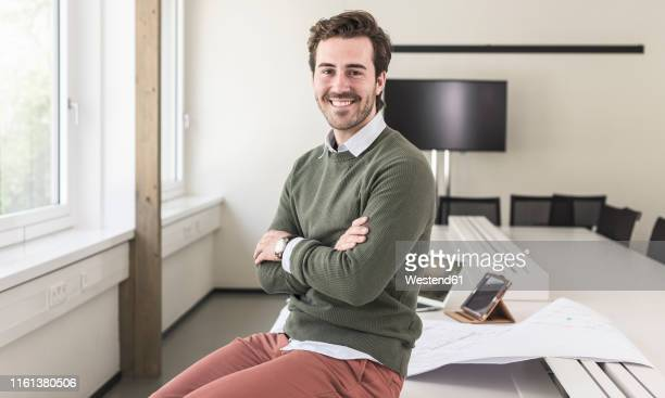 successful, young businessman sitting in boardroom with arms crossed - human body part stock pictures, royalty-free photos & images