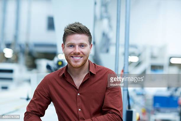 Successful young businessman standing in factory