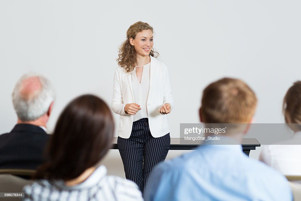 Successful Young Businesswoman Speaking in front of Audience at : Foto de stock