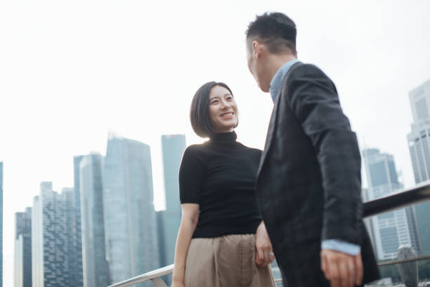 successful young couple talking to each other and standing against urban cityscape in Singapore