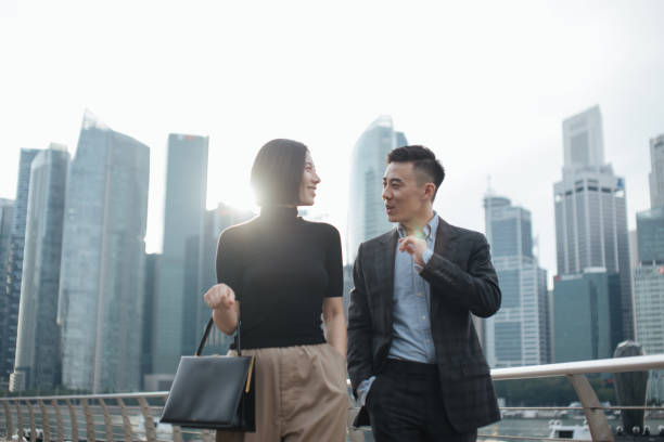 successful young couple talking to each other and walking against urban cityscape in Singapore