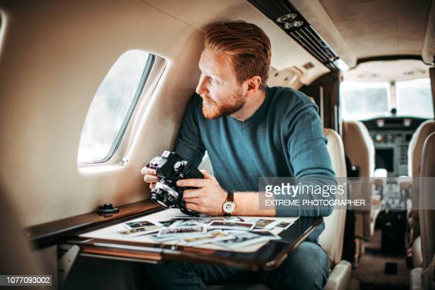 successful young man inside a private airplane looking out of the window while holding a camera - transfer image stock pictures, royalty-free photos & images
