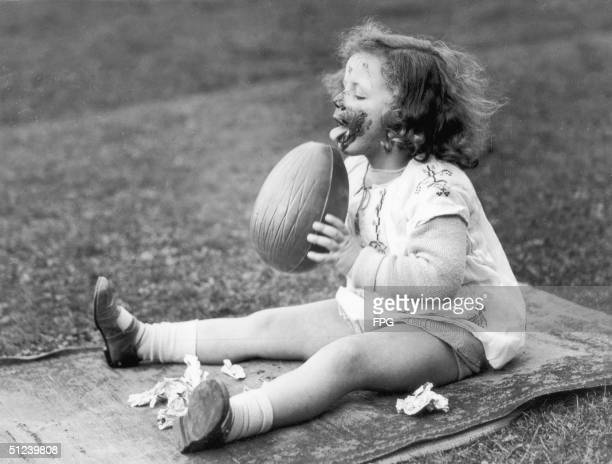 Circa 1930, A little girl makes a pig of herself by licking a large chocolate Easter egg.