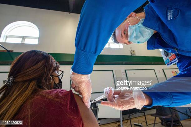 Sucre Lopez receives her second dose of the Moderna Covid-19 vaccine from registered nurse Frederick Morley at a mobile Covid-19 vaccination...