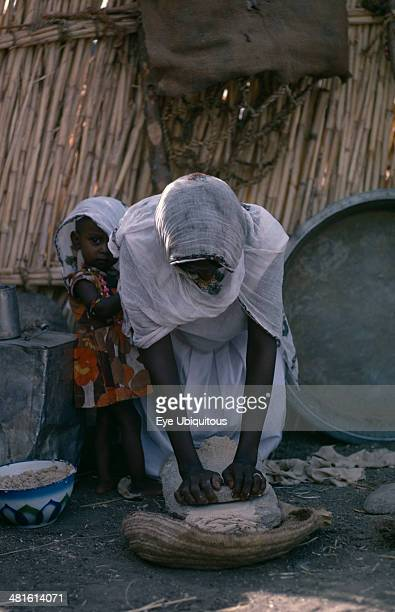 Sudan Food and Drink Woman making bread with young child beside her