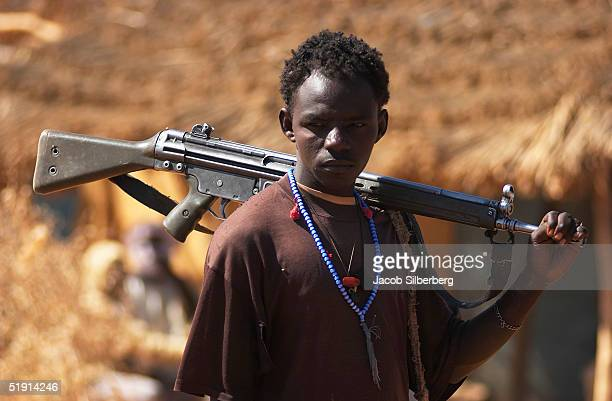 Sudan Liberation Army fighter carries his weapon December 1 2004 in Thabit North Darfur Sudan A recent upsurge in violence between SLA and Government...