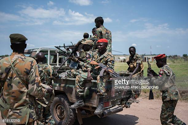 Sudan People Liberation Army soldiers stand on a pick up truck on their way to the river side to ride on a boat on the Nile as they head to Alole...