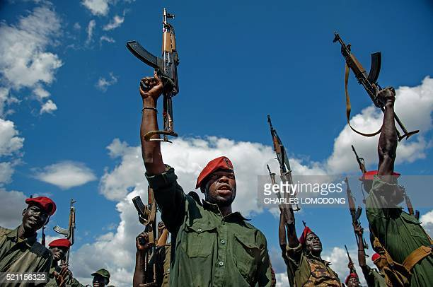 Sudan People's Liberation Army soldiers raise their rifles at a containment site outside of Juba on April 14 2016AFP PHOTO/Charles Atiki Lomodong The...