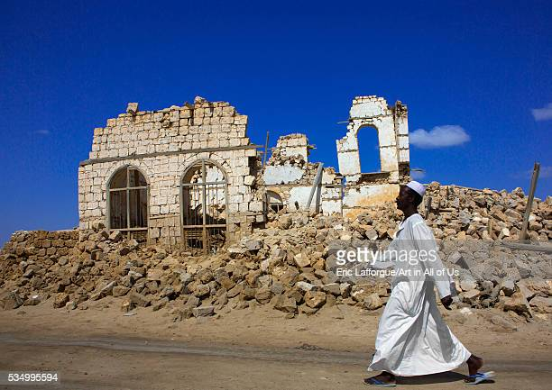 Sudan Port Sudan Suakin man passing in front of a ruined ottoman coral buildings