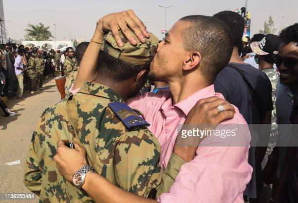Sudanese antiregime protester kisses a soldier on the head during protests on April 11 2019 in the area around the army headquarters in Sudan's...