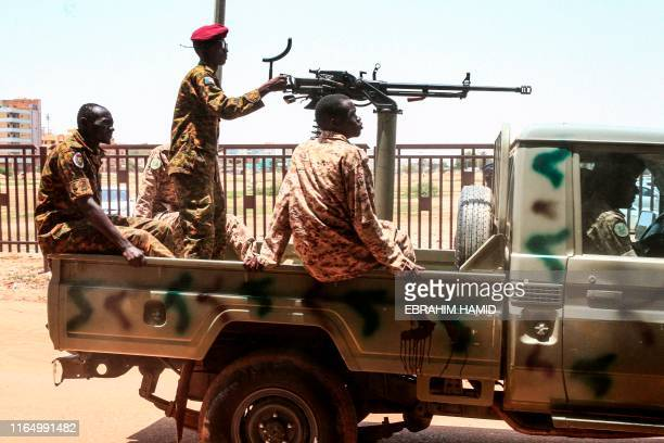 Sudanese army soldiers ride in the back of a technical as they ride in a convoy escorting ex-president Omar al-Bashir back to prison after his...