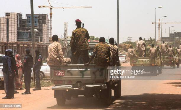 Sudanese army vehicles ride in a convoy escorting ex-president Omar al-Bashir back to prison after his appearance in court in the capital Khartoum on...