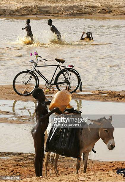 A Sudanese boy loads water on a donkey from a nearby river while others play in the water close to the Internally Displaced Persons camp of Krindng...