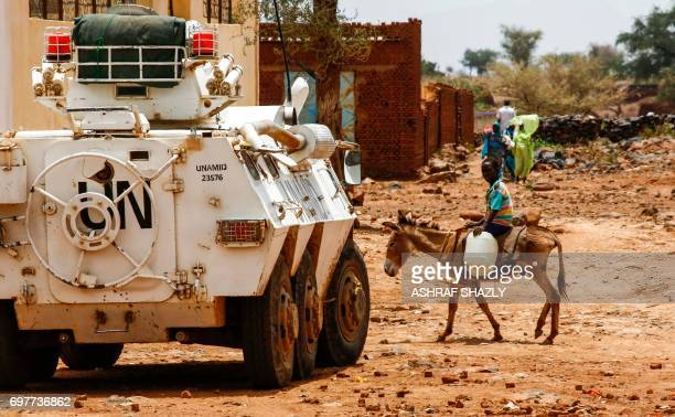 Sudanese boy rides a donkey past a UNAfrican Union mission in Darfur armoured vehicle in the wartorn town of Golo in the thickly forested mountainous...