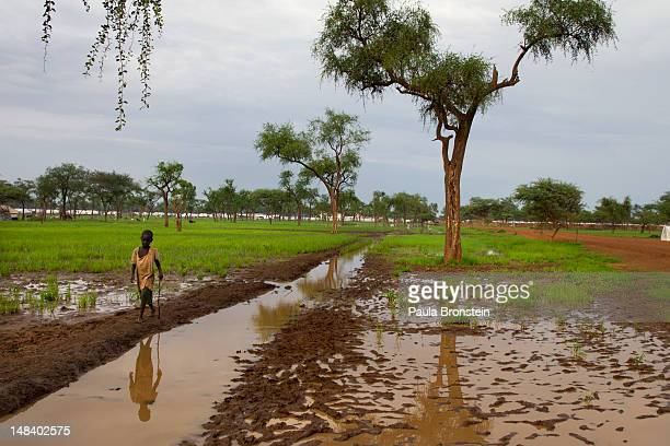 Sudanese boy walks along the muddy field flooded from the rains July 15, 2012 in Jamam camp, South Sudan. Up to 16,000 refugees are in the process of...