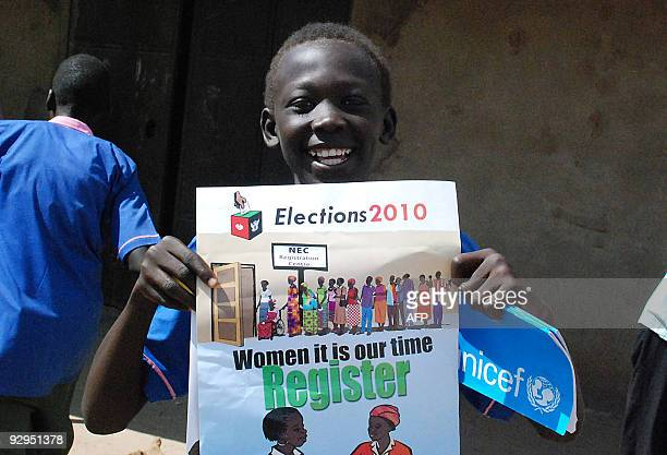 A Sudanese child holds a poster to mark the launch of voter registration for the upcoming elections in the southern capital of Juba on October 31...