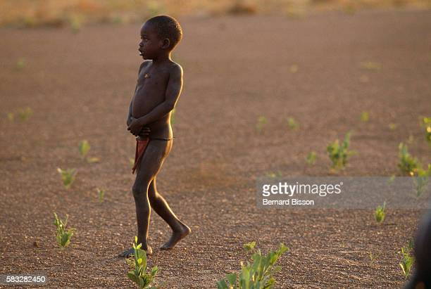 A Sudanese child wearing a red loincloth wanders in the desert around the refugee camp of Kitgun located on the border between Sudan and Uganda where...