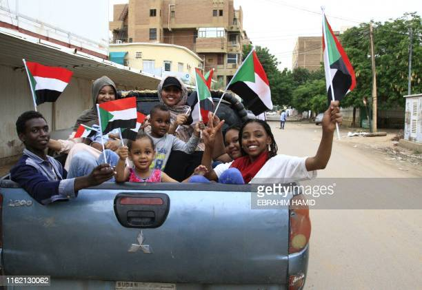TOPSHOT Sudanese children wave small national flags as people celebrate outside the Friendship Hall in the capital Khartoum where generals and...