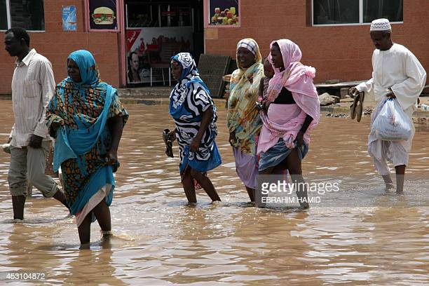 Sudanese cross a flooded street following heavy rain on August 3 2014 in the capital Khartoum More than 3000 homes have been destroyed by floods that...