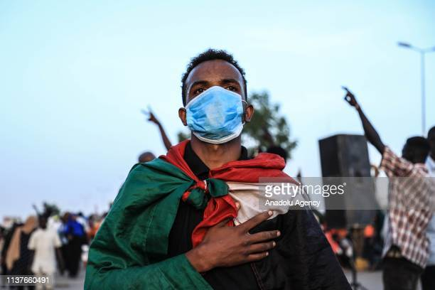 Sudanese demonstrator, wearing a flag as a cape and a face mask, takes part in a demonstration demanding a civilian transition government, in front...