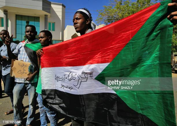 Sudanese demonstrators carry placards and wave their country's national flag as they gather to protest outside the Foreign Ministry in the capital...