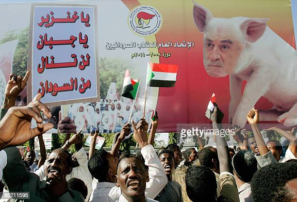 Sudanese demonstrators hold up a poster picturing Chief International Court of Justice Prosecutor Luis Moreno Ocampo as a pig during a demonstration...