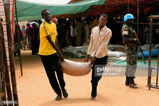 Sudanese displaced men carry food supplies after receiving from a food distribution center as a UnionUnited Nations Mission in Darfur soldier stands...