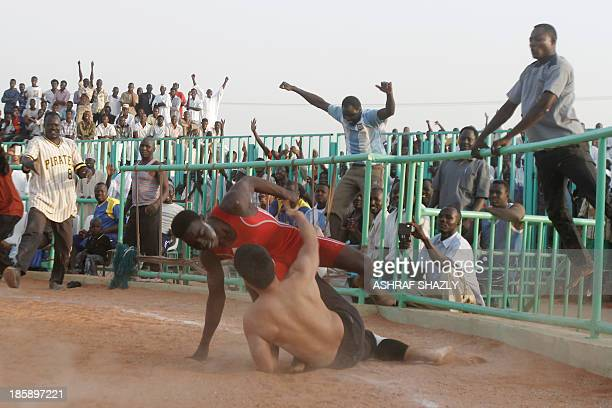 Sudanese fighter alModreya competes against Japanese diplomat Yasuhiro Murotatsu known as Muro in a traditional Sudanese Nuba wrestling match on...