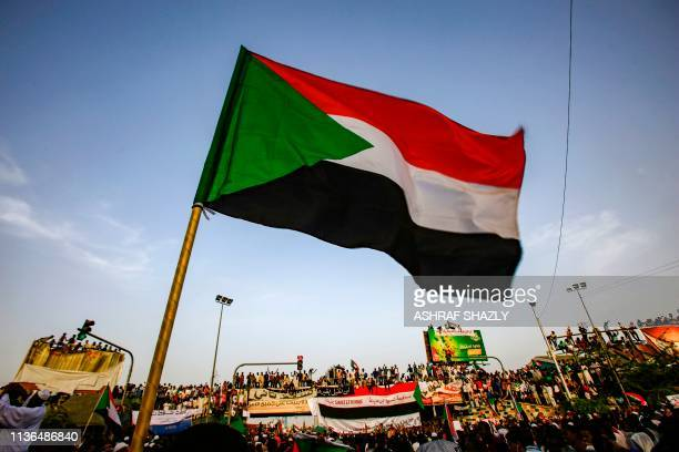 A Sudanese flag is seen waving as protesters chant slogans during a demonstration demanding a civilian body to lead the transition to democracy...