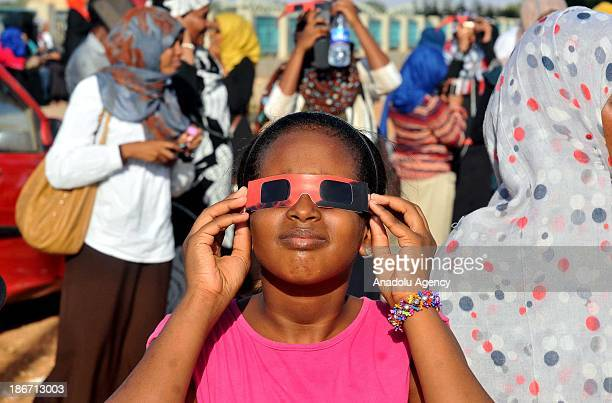 Sudanese girl uses a special viewing glasses to observe a partial solar eclipse over the Sudanese capital Khartoum on November 3 2013 A rare solar...