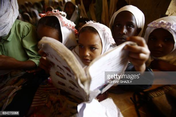 TOPSHOT Sudanese girls sit in a classroom at the ElRiyadh camp for internally displaced persons in Geneina the capital of the state of Sudan's West...