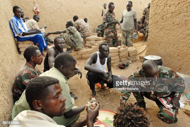 Sudanese government soldiers eat in a prison in Iriba in northeastern Chad October 14 2006 Fierce fighting continues between Sudanese government...
