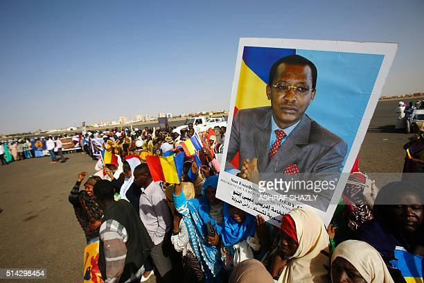 Sudanese hold placards bearing portraits of Chadian President Idriss Deby before his arrival at Khartoum's airport for an official oneday visit on...