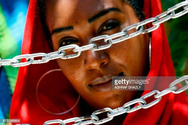 A Sudanese journalist poses with chains as she and others gather outside the Tayar newspaper to announce their intention to begin a hunger strike on...