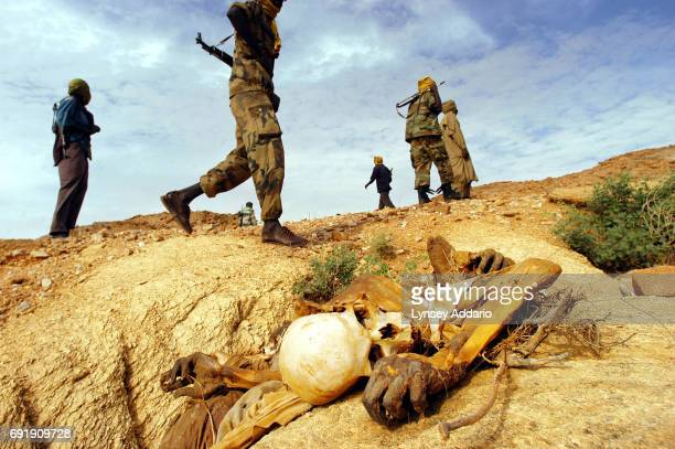 Sudanese Liberation Army soldiers walk past a dead body left from an attack on civilians in the district of Farawyaiah, Darfur, August 24, 2004....