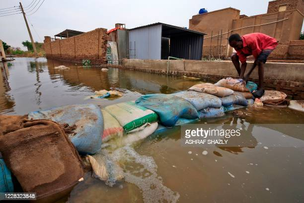 Sudanese man build a barricade amidst flood waters in Tuti island, where the Blue and White Nile merge between the twin cities of the capital...