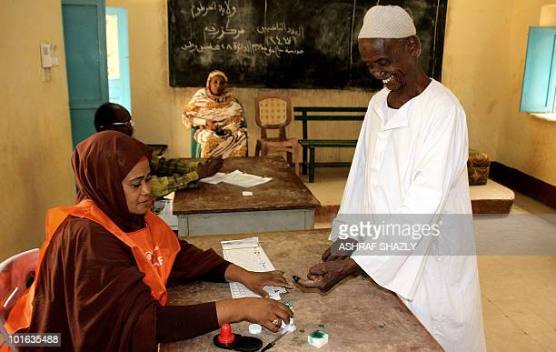 A Sudanese man dips his finger in ink as he arrives to cast his ballot at a voting station in Khartoum on June 5 2010 during a reelection for the...