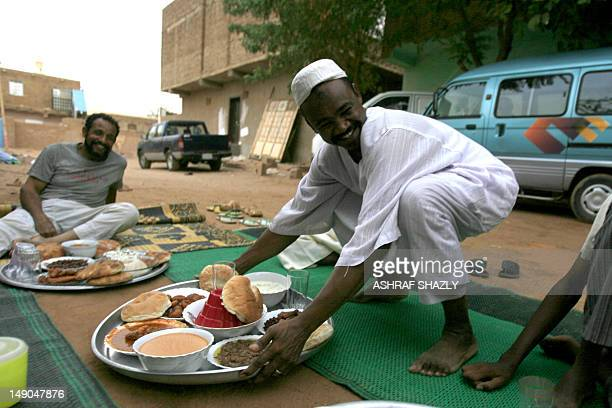 A Sudanese man lays a tray of food as Muslims ready to break their fast as they sit along a street in West Jarif some 7 kilometers east of the...