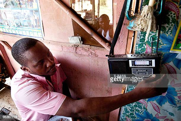 Sudanese man listens to the Radio Miraya show Betna Weekend edition at a shoe repair shop in the southern Sudanese city of Juba on April 10 2010 The...