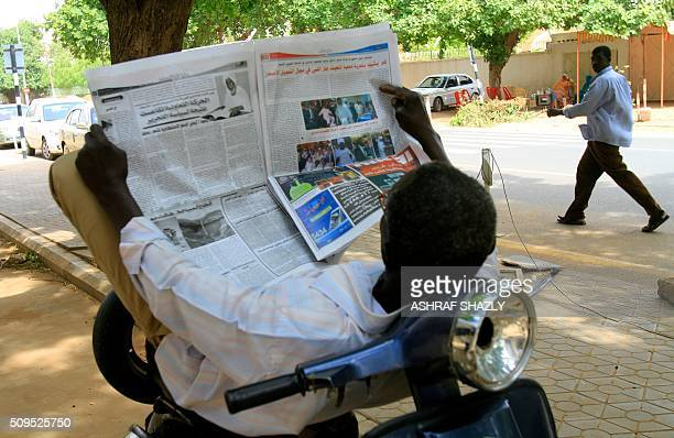 Sudanese man reads a newspaper as he rests on his moped in the capital Khartoum, on July 31 as fears of tighter press freedom in the wake of South...