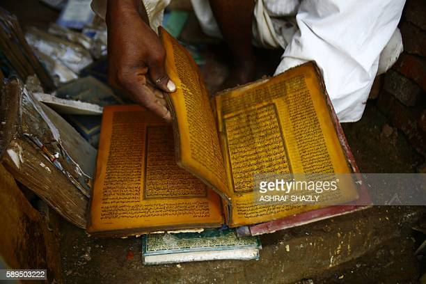 Sudanese man retrieves a Koran Islam's holy book inside a flooded mosque in the village of AlMahmoudab on August 14 in the impoverished eastern state...