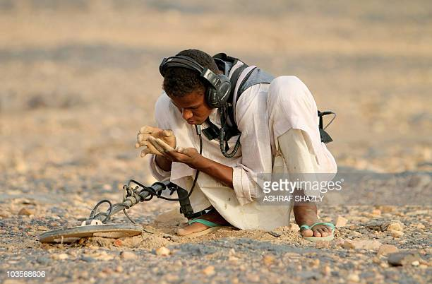 Sudanese man searches for gold with the help of a metal detector in the desert near the village of alShirik in northern Sudan on August 8 2010 Rising...