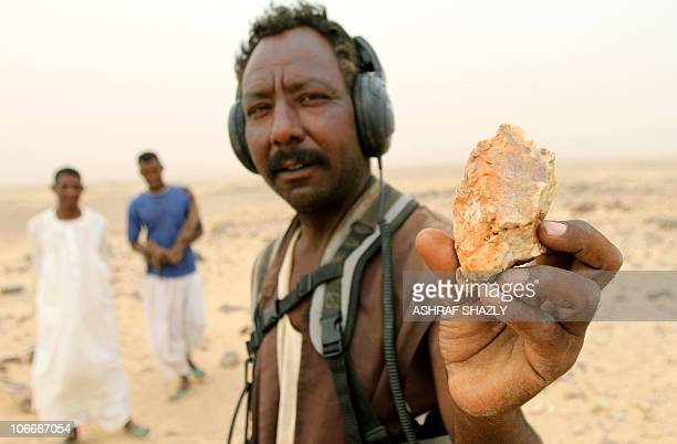 Sudanese man shows a stone with traces of gold in the desert near the village of alShirik in northern Sudan on August 8 2010 Rising gold prices...