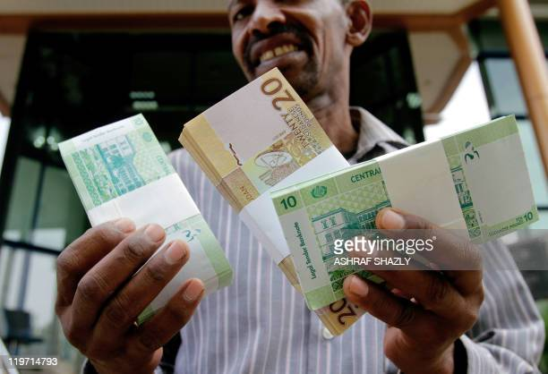 A Sudanese man shows freshlyminted notes of the new Sudanese pound in Khartoum on July 24 2011 as the country issues new currency following the...