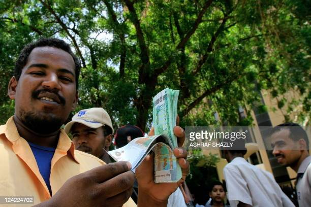 A Sudanese man shows off the new currency in front of Central Bank of Sudan in the capital Khartoum on August 27 several weeks after Sudan launched...