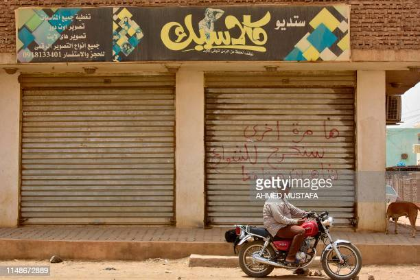 Sudanese man sits on a motorbike in front of a closed photo studio in Khartoum on June 9 2019 Arabic writing on the shutters of the closed shop reads...